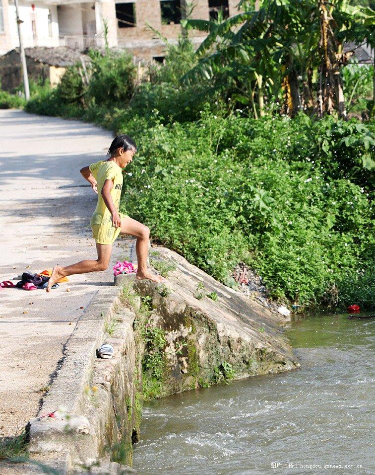实拍乡下儿童小溪边玩跳水图片